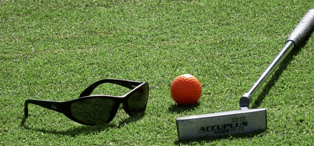 Golf club, golf ball and sunglasses