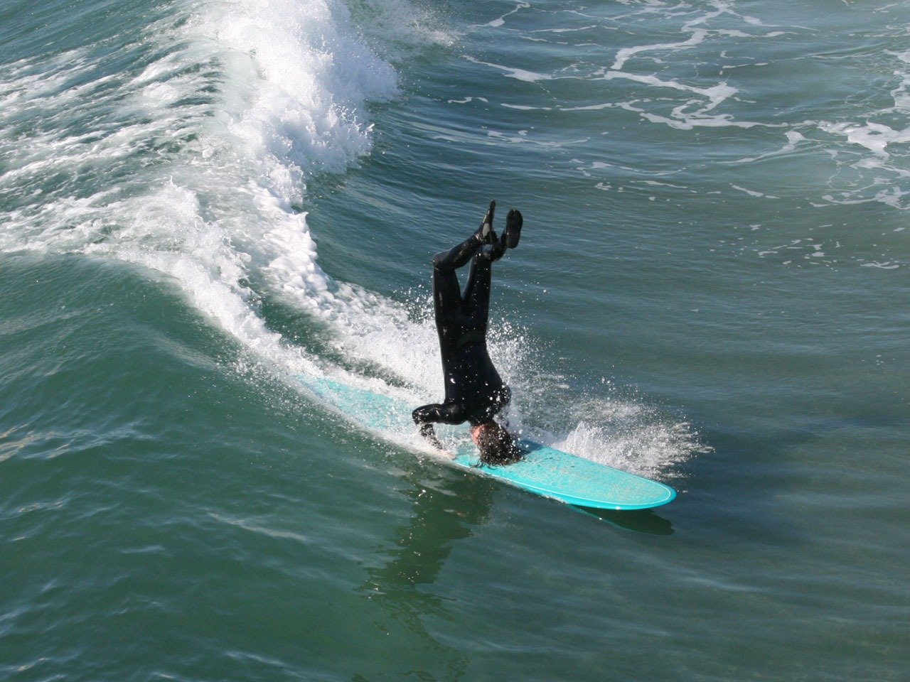 Guy surfing on his head in Huntington Beach, California's Surf City